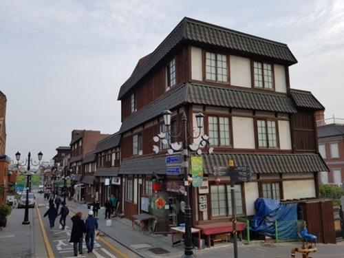 日本式の建物が並ぶ商店街を観光客が歩いている。