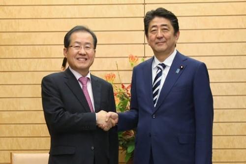 自由韓国党の洪準杓代表(左)が14日午後、東京の首相官邸で安倍晋三首相と握手をしている。2人はこの日、北核問題の解決に向けた両国間協力案を議論した。(写真=自由韓国党)