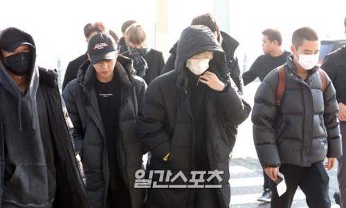 21日午前、硬い表情で仁川国際空港に姿を見せたEXOのメンバー。