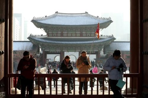 21日午後、ソウル景福宮(キョンボックン)を訪問した中国人団体観光客がガイドの説明を聞いている。