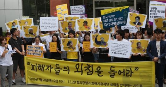 和解・癒し財団の懸板式が開かれた2016年7月、建物の前で反対団体がデモを行った。