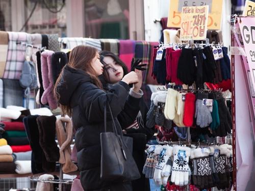 弘大(ホンデ)のファッションショップの店先では、真冬の韓国でかかせない手袋などのあったか小物を買い求める人の姿が見られます。