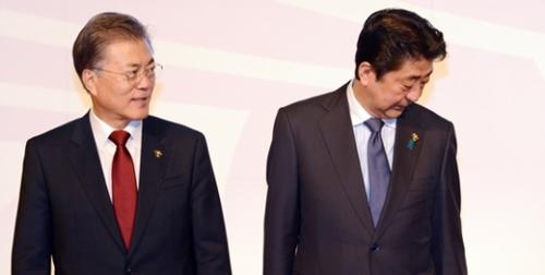 文在寅(ムン・ジェイン)大統領と安倍首相が昨年11月14日、フィリピン・マニラの国際コンベンションセンターで開催されたASEANプラス3首脳会議の記念撮影で並んで立っている。(青瓦台写真記者団)