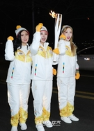 16日、ソウル汝矣島IFCモール付近を聖火を手に走っているガールズグループのMAMAMOO(ママムー)。