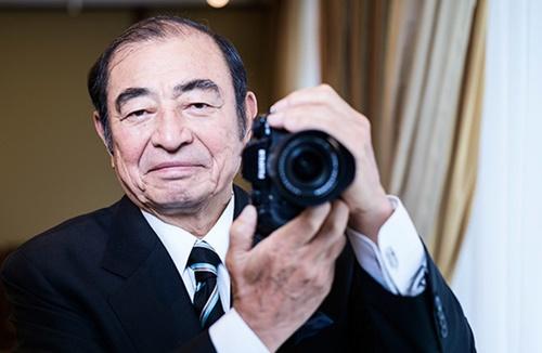 富士フイルムホールディングスの古森重隆会長がカメラを持ってポーズを取っている。本業であるフィルム事業をあきらめる構造調整で会社を回復させた古森会長は最近、米ゼロックスの買収計画を発表した。(写真=中央フォト)