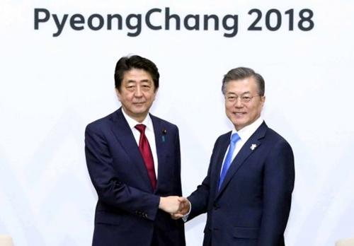 文在寅大統領と安倍首相が平昌で開かれた韓日首脳会談に先立ち、握手を交わしている。