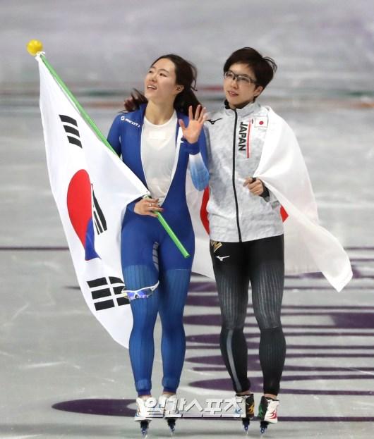 2018年平昌冬季五輪スピードスケートの競技が18日午後、江陵スピードスケート競技場で開かれた。スピードスケート女子500mに出場した李相花が銀メダルを確定した後、太極旗を手に観衆の応援に応えている。その横は金メダルを獲得した日本の小平奈緒。