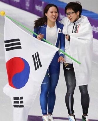 18日、江原道江陵スピードスケート競技場で行われた平昌冬季五輪スピードスケート女子500メートル競技の後、肩を寄せ合いながらリンクを回る韓国の李相花(左)と日本の小平奈緒。