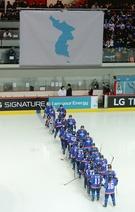 南北女アイスホッケー合同チームが4日午後、仁川仙鶴リンクでスウェーデンと親善評価試合を行った。統一旗が掲げられている競技場に南北合同チームの選手たちが入場しながらハイタッチををしている。(写真=共同取材団)
