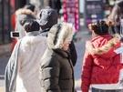 ファー付きのフードや帽子をすっぽりかぶって顔や頭までしっかりガードする人の姿もちらほら。