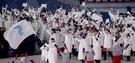 南北選手が9日、平昌オリンピックスタジアムで開かれた2018年平昌冬季五輪開会式で韓半島の旗を持って入場している。(写真=共同取材団)