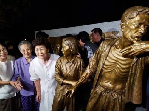 日本による植民地時代に強制徴用された労働者を象徴する強制徴用労働者像「解放の予感」が2017年8月12日、全国で初めて仁川の富平公園に設置された。銅像の「娘」のモデルとなったチ・ヨンレさん(左端)と「父」のモデルのイ・インヒョンさんの娘イ・スクチャさん(左から2人目)が銅像の前で記念撮影をしている。