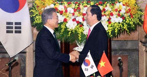 韓国の文在寅大統領とベトナムのチャン・ダイ・クアン国家主席が23日午前(現地時間)、会談場であるハノイ主席宮で開かれた共同記者会見終了後、両手を取り合っている。(写真=青瓦台写真記者団)