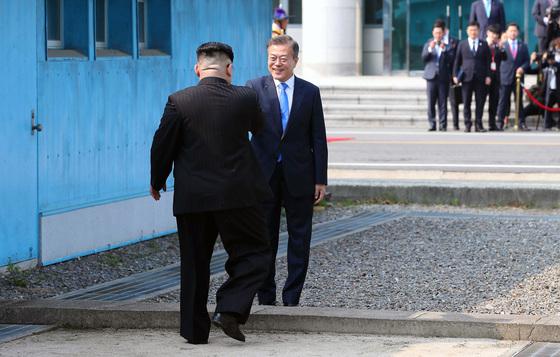 板門店(パンムンジョム)軍事境界線で会い、握手を交わした南北首脳。