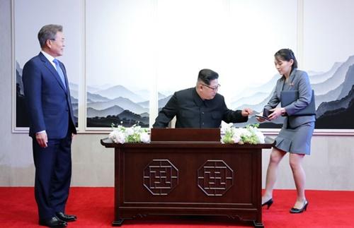文在寅大統領が27日午前、板門店「平和の家」で芳名録に記帳する北朝鮮の金正恩国務委員長を見ている。金与正党中央委第1副部長が隣で金委員長を補佐している。