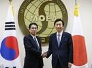 2015年12月28日、ソウル外交部庁舎で韓国の尹炳世外交部長官(右)と岸田文雄前外相が慰安婦問題の解決策をさぐる会談に先立ち、握手をしている。