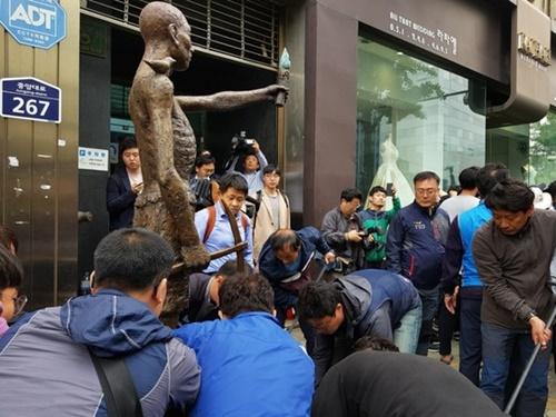 市民団体の会員らが1日午前9時40分、日本総領事館前に労働者像を移している。
