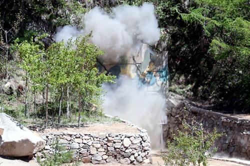 24日、北朝鮮核兵器研究所の関係者らが豊渓里核実験場を閉鎖するための爆破作業をした。2番坑道の爆破の瞬間、坑道の外に煙が出ている。(写真=共同取材団)