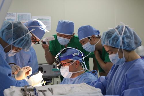 パク・ジェホン教授(真ん中)が緑の手術衣を着た2人の日本人医療スタッフが参観する中、「後耳介甲状腺切除術」をしている。(写真=提供)