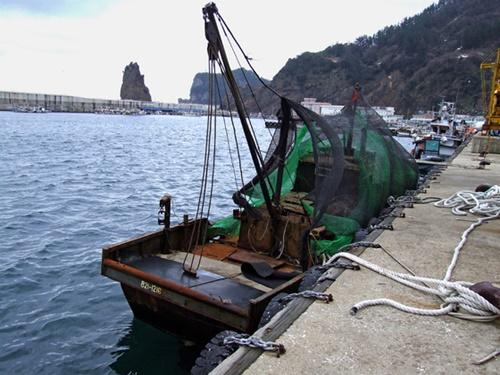 2014年に鬱陵島(ウルルンド)沖で漂流しているところを韓国海軍に発見された北朝鮮船が鬱陵島の港に曳航されている。この漁船は長さ14メートル、幅3.2メートル、高さ5メートルの15トン級で、見つかった当時は船員がいなかった。(写真提供=慶北日報]