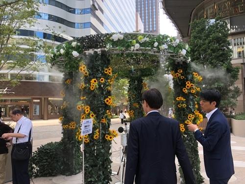 23日、東京日比谷で開かれた暑さ対策展で市民が「ミストシャワー」などを試している。東京の都心はこの日、39度まで気温が上がった。