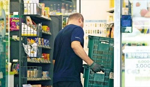 急激な最低賃金引き上げの余波でコンビニ運営が難しくなり新規契約を断念する事例が相次いでいる。ソウル・中区のあるコンビニで店主が商品を移動している。