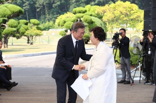 文在寅大統領が14日、忠南天安国立望郷の丘牡丹墓地で開かれた「日本軍慰安婦被害者をたたえる日」行事で慰安婦被害者の李容洙さんの手を握っている。(写真=青瓦台写真記者団)