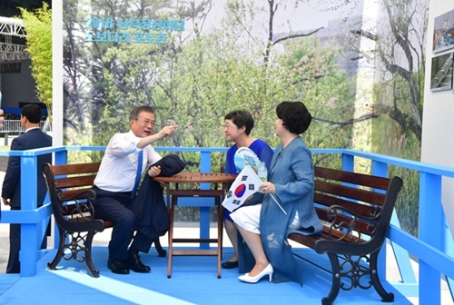文在寅大統領と金正淑夫人(右)が15日、光復節慶祝式を終えた後、徒歩橋の模型でイ・ソヨン国家記録院長と話を交わしている。(写真=青瓦台写真記者団)