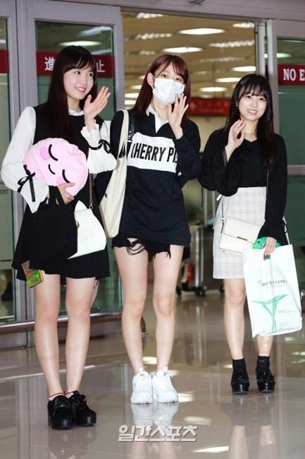 26日午前、金浦空港入国フロアで取材陣に対してポーズを取っている韓日女性アイドルグループIZ*ONEの日本人メンバーの(左から)本田仁美、宮脇咲良、矢吹奈子。