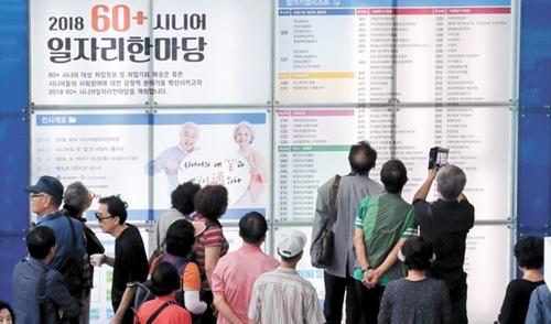 19日、釜山海雲台区BEXCOで開かれた「60(60歳以上)シニア雇用フォーラム」で高齢者らが採用情報を調べている。この行事は115社が中高年・高齢の求職者1238人を採用するために開かれた。