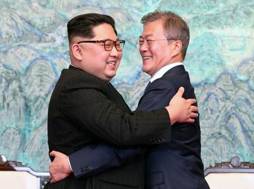 韓国の文在寅大統領(右)と北朝鮮の金正恩国務委員長が、4月27日の南北首脳会談で「板門店宣言文」に署名後、明るい笑顔で抱擁している。(写真=青瓦台写真記者団)
