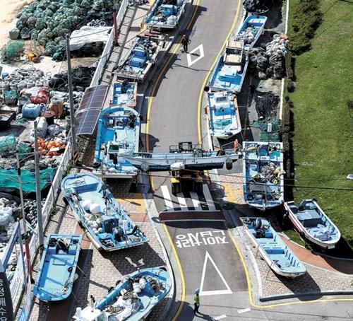 4日、台風25号が接近する中、釜山海雲台区の松亭海水浴場で、漁民がフォークリフトで小型漁船を移動させている。