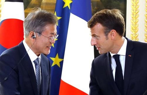 フランスを国賓訪問中の文在寅(ムン・ジェイン)大統領が15日午後(現地時間)、エリゼ宮(大統領府)でマクロン仏大統領と首脳会談を終えた後、共同記者会見で握手している。(青瓦台写真記者団)