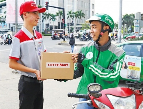 <1時間以内「弾丸配送>ロッテマート南サイゴン店のスタッフがグラブのバイクドライバーに顧客が注文した商品を渡している。