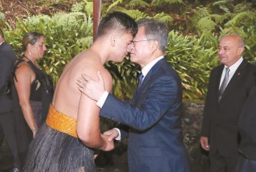 ニュージーランドを国賓訪問中の文在寅大統領が3日(現地時間)、総督官邸で開かれた公式歓迎式で、マオリ族の公演者と握手しながら鼻を合わせるホンギ(Hongi)であいさつしている。文大統領は歓迎に感謝の言葉を伝えた。(青瓦台写真記者団)
