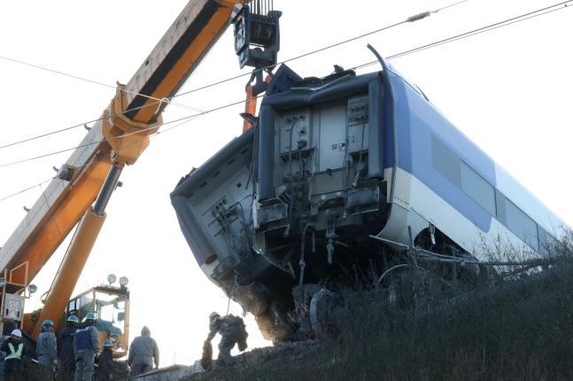 8日午後、起重機などを動員して脱線したKTX列車がつり上げられている。