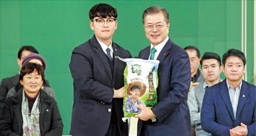 文在寅大統領が27日、青瓦台迎賓館で開かれた農業人招請懇談会で、中学生ハン・テウン君(15)が収穫したコメ5キロを受けている。ハン君は京畿道安城で祖父の農作業を手伝ってコメを収穫した。