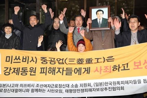 昨年11月29日、韓国最高裁が三菱を相手にした強制徴用被害者の損害賠償請求訴訟で原告勝訴判決を出し、朝鮮女性勤労挺身隊被害者のキム・ソンジュさん(前列の真ん中)をはじめとする徴用被害者が喜んでいる。(中央DB)