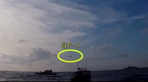 韓国国防部が4日、韓日「レーダー葛藤」をめぐる日本側の主張に反論する動画をYouTubeに公開した。写真は遭難船舶救助作戦中の駆逐艦「広開土大王」の上空から低高度に進入した日本哨戒機の様子(黄色い囲みの中)を海洋警察が撮影した映像だ。(写真=韓国国防部YouTubeキャプチャ)