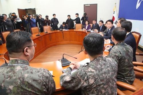 24日、共に民主党の趙正シク政策委員長(太極旗の前)が、国会で軍関係者から日本哨戒機近接飛行関連の報告を受けている。
