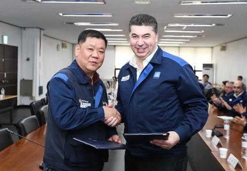昨年の賃金および団体協約調印式で握手を交わしたカゼム韓国GM社長(右)とイム・ハンテク全国金属労働組合韓国GM支部長。(写真=韓国GM)
