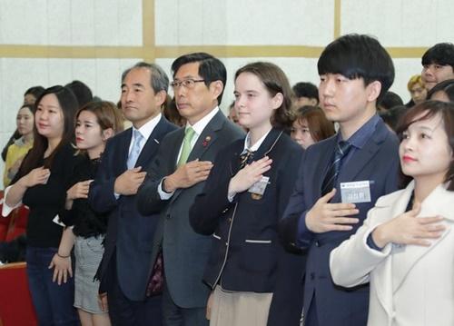 朴相基(パク・サンギ)法務部長官(中央)が先月21日、ソウル龍山区(ヨンサング)国立ハングル博物館大講堂で開かれた第1回大韓民国国籍証書授与式で国旗に対し敬礼をしている。