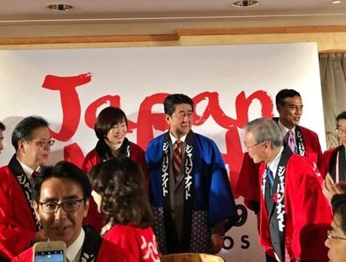 1月24日、スイス・ダボス会議で開かれた「ジャパン・ナイト」行事で舞台に立つ安倍首相(青い法被)と日本の政界・財界人。