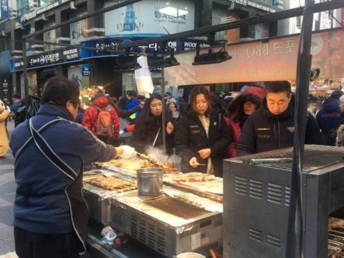 今月7日、ソウル中区明洞で中国人観光客がストリートフードの店でものを買って食べている。商人は「昨年の春節よりも観光客が減った」と話した。