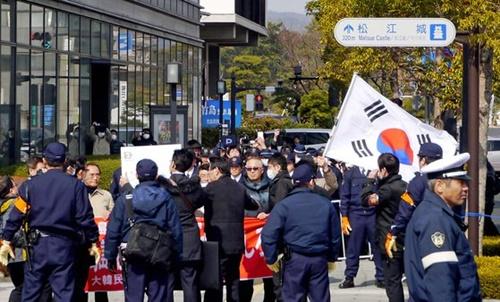 2013年、島根県主催の「竹島の日」行事が開かれた県民会館の外で、独島守護全国連帯など韓国の市民団体会員が日本の警察に囲まれながら太極旗を持って抗議デモをしている(中央フォト)。