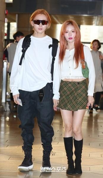 18日午前、金浦空港で取材陣に向かってポーズを取っている歌手のイドン(左)とヒョナ。