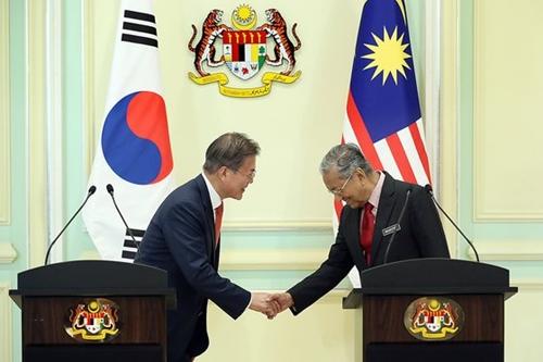 マレーシアを国賓訪問中の文在寅大統領が13日午後プトラジャヤの首相官邸で合同メディア発表を終えた後、マハティール・ビン・モハマド・マレーシア首相と握手している。(写真=青瓦台提供)