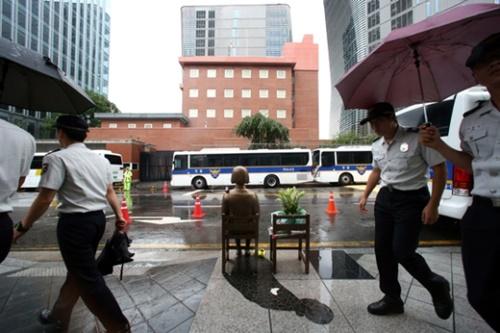 撤去前の在韓日本大使館とその前に設置されている平和の少女像