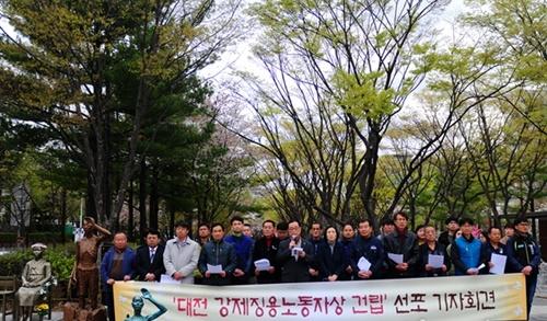 釜山の強制徴用労働者像。市民団体のメンバーが記念写真を撮影している。