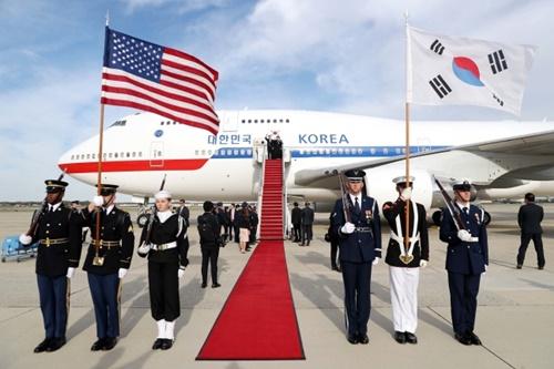 韓国の文在寅大統領が韓米首脳会談のために11日午前(現地時間)、米国アンドルーズ空軍基地空港に到着して挨拶をしている。写真右上の儀仗隊の太極旗の青色の部分が空色になっている。